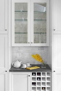 Palmerston Design Creamy white shaker kitchen cabinets painted Benjamin Moore Chantilly Lace, Caesarstone quartz countertops, calcutta marble subway tiles backsplash and built-in wine rack..