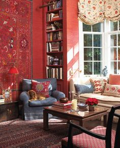 seems like such a comfy, cozy room! . Anne Hepfer deep coral walls..built in bookcase...wall hanging..comfortable seating..bay window...