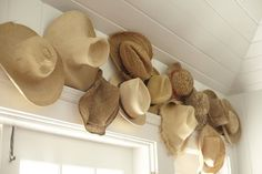 An interview with India Hicks and a look at her recent collaboration with Pottery Barn. Hat collection, straw hat hanging, display of sun hats
