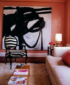 Luxuriate in the Living Room. Coral walls, a zebra print chair, and an oversized black and white abstract painting. Interior Designer: Miles Redd.