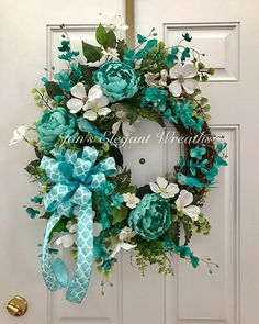 Here is a gorgeous large, aqua Spring wreath! Three large, aqua peonies, springy white orchids, lots and lots of green foliage and finally, a large bow of aqua and white quatrefoil pattern ribbon make up this beautiful Spring wreath for your front door, or foyer, or living room!