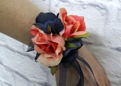 This coral rose wrist corsage is made from the finest quality silk flowers. Weddings, proms or any formal occasion this corsage adds the perfect finishing touch. Corsage is designed with 2 sweetheart coral roses and accent hydrangea, with coordinating ribbon trailers. Choose from rhinestone, white or ivory pearl bracelet, select small pearls for small to medium wrists, large pearl bracelet for medium to large wrists. Coordinating wedding bouquet…