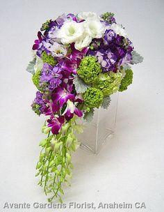 Cascading bride's bouquet featuring lisianthus, orchids, viburnum and stock.