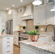 A neutral colored kitchen looks clean and fresh. The patterned backsplash doesn't overpower the room, and looks great against the countertops too!