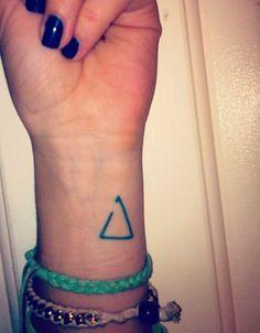 """Símbolo Delta incompleto  El símbolo Delta significa """"cambio"""". En este caso, si le falta un poco para estar cerrado, significa: """"Abierta al cambio""""."""