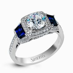Featuring an elegant classic design, this white gold engagement ring is set with .23 ctw round cut white diamonds and side accents of .62 ctw trapezoid cut sapphires.