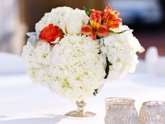 CD Florals created these white hydrangea centerpieces with touches of coral in mercury glass containers. | 4.9.2016 at The Sonnet House | Photo by Be Light Photography