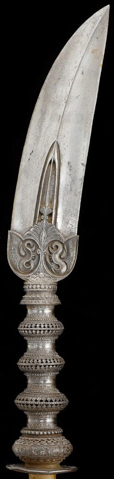 Indian (Mysore) javelin blade, 17th century, slightly curved, tapering steel blade on a turned baluster haft, the forte incised with symmetrical elaborate floral and vegetal motifs, mounted on to a long wooden shaft blade 56 cm. long.