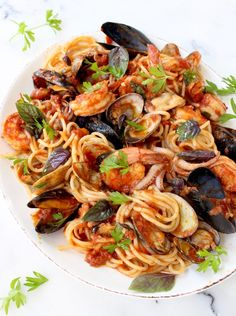 The ultimate spaghetti Frutti di Mare (Seafood Spaghetti) recipe, made with baby clams, mussels, squid and shrimp in a thick red Arrabiata sauce. Seafood spaghetti, better than your favorite Italian restaurant.