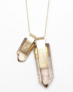Large natural chunks of smokey quartz, wrapped in hammered brass and hung from a lengthy gold ball chain, from Nallik.