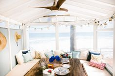 Hanging string lights gives this seating area a sense of coziness, while the blue and white pillows (and that one pop of red!) lend those Americana vibes.