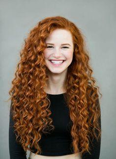 cheveux cuivré, femme souriante avec lèvres rose, sourcils peint en cuivre, cheveux longs et bouclés, blouse noire avec manches longues