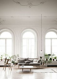 Fresh white sparse minimal living room. Big grand windows. Potted green plants.