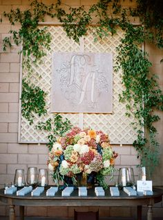 Guests found their table assignments on a wooden table topped with candles and a large arrangement of hydrangeas.The couple's monogram was carved into wood and placed on a wall of vines. #RusticDecor Photography: Elisabeth Millay Photography. Read More: http://www.insideweddings.com/weddings/romantic-neutral-hued-wedding-at-a-paso-robles-california-vineyard/585/