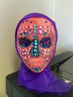 Child's entry - 'Mask of Courage' - My mum [ the colours on the face are to show the pain, fear and worry she went through when she had breast cancer. The jewels show the mask she put on every day to protect me, like nothing was wrong.