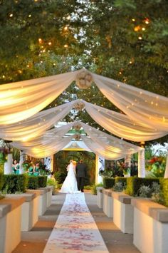 This got a wow from us. Either over the ceremony or the reception area, lit swags of fabric and twinkle lights in the trees above. Lovely.