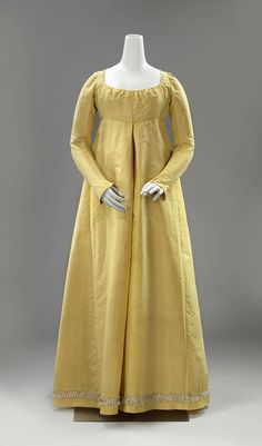 Gown of canary yellow silk with high waist, diamond-shaped back yoke, long sleeves and along the rokzoom trimmed with white and yellow silk trimmings with tassels, ca. 1790 - ca. 1810