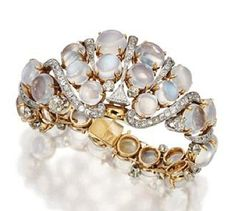 MOONSTONE AND DIAMOND BRACELET, CIRCA 1940. The partly flexible, tapering bracelet set with 26 round cabochon moonstones and accented with scrolls of 60 old-mine diamonds weighing approximately 5.00 carats, the center set with a single triangular-shaped diamond of approximately .90 carat, mounted in pink gold, length 7 inches.
