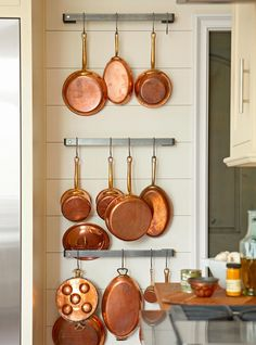 Fill empty kitchen walls with cooking essentials that double as decor. Pots, pans, baking supplies, and utensils make great wall art when hung in multiples. #decorideas #upcycledecor #homedecor #kitchendecor #bhg