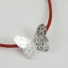 Collar mariposa con marcas en forma de corazón. Plata de ley en un cordón de seda japonesa que resulta elegante y, a la vez, llamativamente sutil.   Un toque de gracia que realzará tu belleza.