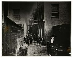 """Jacob Riis, Mullen's Alley, February 12, 1888 -.....Mulberry Bend was near the dangerous Five Points area and the buildings were crowded together and unsafe: """"The whole district is a maze of narrow, often unsuspected passage ways—necessarily, for there is scarce a lot that has not two, three, or four tenements upon it, swarming with unwholesome crowds."""" The Bone Alley block had a population of about 1,000 people per acre, creating dangerous and disease-ridden conditions."""