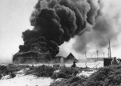 Black smoke rises from burning U.S. oil tank,set afire during Japanese air raid on Naval Air Station Midway,4Jun1942