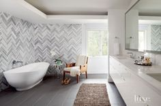Architect Caroline Wilding laid this master bathroom's wall tiles by Emser Tile in a graphic herringbone pattern. An existing wood armchair, a side table from Columbine Showroom and a Tyrrell & Laing International freestanding tub all rest on Cebu Silver matte floor tiles from Arizona Tile. #LuxeTurns10