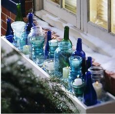 For a striking display cluster colored and clear glass bottles, jars, and vintage insulation glass in an outdoor window box. Vary heights, shapes, and colors for visual interest. Insert votives or flickering battery-operated candles Christmas Window Boxes, Winter Window Boxes, Christmas Window Decorations, Bottle Decorations, Outdoor Decorations, Indoor Window Boxes, Window Sill, Room Window, Glass Insulators