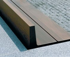 simple wood bench inset into concrete/stone (?) wall