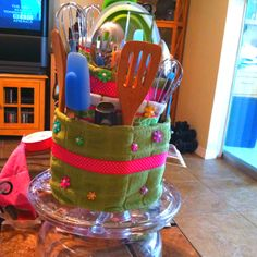 """Wedding shower gift using the brides gift registry pick utensils that will fit in the """"cake"""" dish towels and the base is a glass cake dome add some ribbon and you have a creative gift that looks like a cake"""
