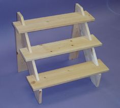 """3 Step Wood Riser 23""""W x 17""""H x 18""""D with 6"""" steps. Natural finish. You may stain or paint. Ships flat in one box. Ideal for trade shows."""
