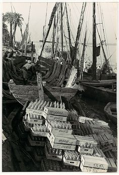 Cases of Coca-Cola Bottles on Bank of River with Sailing Vessels,1940s. Photo by Henri Cartier-Bresson.