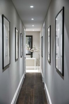 Modern contemporary hallway design and decor. Grey hallway walls, hardwood floors and bright LED recessed lighting. Hanging pictures in a narrow hallway. Hallway Colours, Lobby Design, Home, Entryway Lighting, Entryway Decor, Hallway Lighting, Hallway Wall Decor, Home Interior Design, Narrow Hallway Decorating