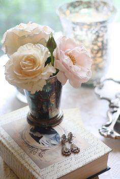tabletop vignette of pale roses, old silver, vintage earrings and books - this is me!