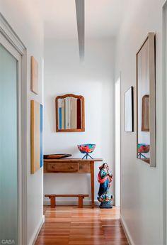 O corredor cheio de obras de arte conduz aos quartos. Ao fundo, junto ao aparador e à banqueta (Marcenaria Baraúna), a escultura da Nossa Senhora veio de uma feira no interior paulista. O espelho é herança da mãe.
