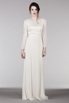 Our play on a long sleeved wedding dress, this elegant and modern dress has a plunge back with a layered front neckline and one-of-a-kind floral hand embroidery that cascades down the front bodice as