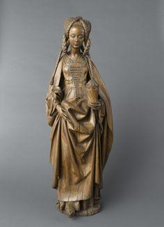 1475 À l'origine éclatante de couleur, décapée et teintée au XIXe siècle, cette figure de Marie-Madeleine a bénéficié d'un récent décirage. Seuls d'infimes vestiges de cette polychromie permettent de reconstituer la coloration rouge et bleue de sa robe.