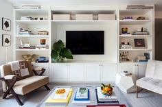 Beautiful living room features a wall fitted with floor to ceiling built in media center boasting shelves illuminated by polished nickel picture sconces flanking a shelf filled with woven baskets over a flatscreen TV.
