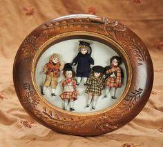 Five dollhouse dolls in shadowbox frame