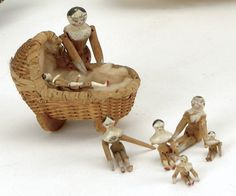 "Germany, ca. 1830, a wonderful group of 8 small jointed wooden dolls approximately 1"" - 1.5"" tall with painted features, 2 contained in wicker woven cradle, largest doll 1.5"" t."