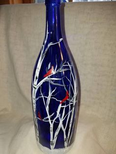 Cardinals in Birch trees hand painted on a cobalt blue wine bottle. This magnificent bottle lights up with 20 led fairy lights strung through a faux cork. The cork has an on/off switch and takes 3 LR44 batteries (included). Thanks for stopping by