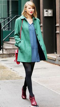 MARCH 28, 2014 Swift braved the cold by pairing her polka dot drop-waist dress with a bold green topper, opaque tights, and oxblood red booties.
