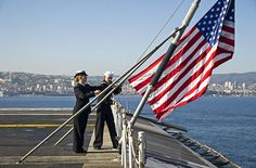 Aviation Boatswain's Mate (Handling) Airman Hannah Werner and Aviation Boatswain's Mate (Handling) Airman Thomas Sallas raise the national ensign on the flight deck of aircraft carrier USS George Washington (CVN 73) as the ship arrives in Valparaiso, Chile for a scheduled port visit.