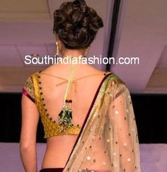 """""""Simple brocade blouse for lehengas and sarees with deep back neck and contrast cloth buttons stitched all around the neck border and complemented by heavy tassels...."""""""