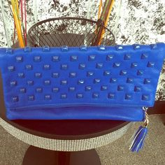 Blue Folder Clutch Bag Blue clutch that has gold hardware chains to make it a strap bag. The bag hasn't been carried , however there are no tags . Has two zipper areas at the fold and inside the fold . Bags Clutches & Wristlets
