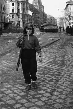 """by Erich Lessing. A burnt-out heavy tank """"Josef Stalin"""" IS 3 with a 122 mm gun near the Kilian barracks in Budapest. An insurgent walking home. After the defeat of the Revolution, she was sentenced to death and executed. Insurgent, Budapest Hungary, My Heritage, Women In History, Cold War, Pictures Images, Historical Photos, World War Ii, Wwii"""