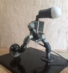 Handmade industrial robot lamp design with functioning light and toggle style switch. Lamp is mounted on a 12 x 11 x 1 piece of pine which is roughly sanded, stained and sealed with black shellac for an antique look. This lamp is hand made in my Brooklyn studio. (and is awesome!)