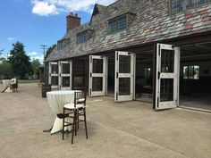 So many ways to use the paved courtyard between the Lodge and the Repair Garage buildings at the Packard Proving Grounds!  A few tall chairs are a nice touch to go along with the high top cocktail tables for those that might like to sit for a bit  the wine barrels add some rustic vintage elegance too.