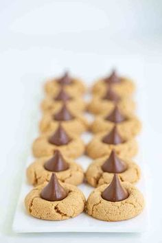 Peanut Butter Blossoms - These are the best Peanut Butter Blossoms! They're made with butter, loads of peanut butter, and the perfect balance of brown sugar and granulated sugar. Pop a chocolate kiss in the center and they're ready for serving! This is the Hershey Kiss Cookie recipe that you have to try! #cookiedoughandovenmitt #peanutbutter #cookies #dessert Peanut Butter Dessert Recipes, Peanut Butter Blossom Cookies, Best Peanut Butter, Candy Recipes, Yummy Recipes, Cooking Recipes, Drop Cookies, Xmas Cookies, Sugar Pop