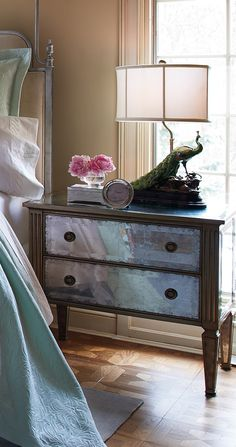 The French technique of eglomise-silver leafing behind glass-creates mirror-like surfaces with Old Hollywood glamour on the Adelaide Eglomise Bedside Chest.